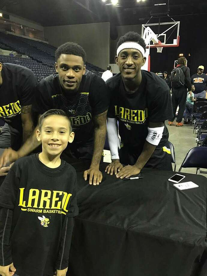 A Swarm fan poses with guards Kevin Jefferson Jr. and Anthony Alston after a game last year. Laredo is set to come back to Laredo Energy Arena for the 2017-18 campaign but still needs to work out some details with the arena and city. Photo: Courtesy Of The Laredo Swarm, File