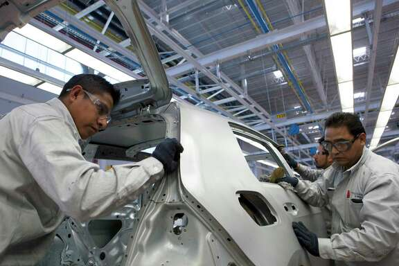 Employees inspect the chassis of a Volkswagen Golf at an assembly plant in Puebla, Mexico.  The U.S. trade representative has released a report about goals for updating the North American Free Trade Agreement.