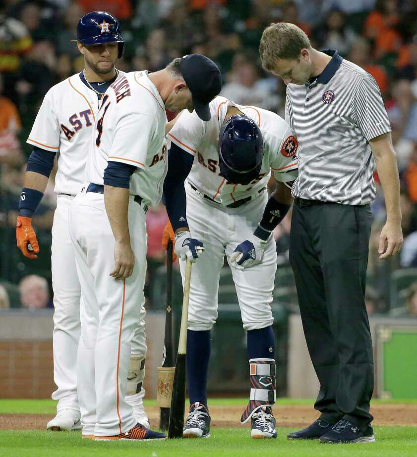Carlos Correa is attended to after suffering a jammed thumb that forced him to depart in the fourth. He will be re-evaluated today. Photo: Melissa Phillip, Staff / © 2017 Houston Chronicle
