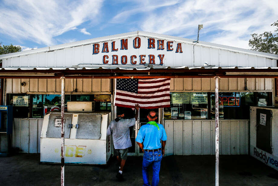 A man places his hand on an American flag as people walk into the Balmorhea Grocery Monday, July 17, 2017 in Balmorhea. (Michael Ciaglo/Houston Chronicle)