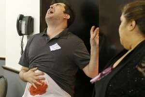 """Actor Andrew Martinez plays one of the victims during a performance of """"The Dinner Detective."""""""
