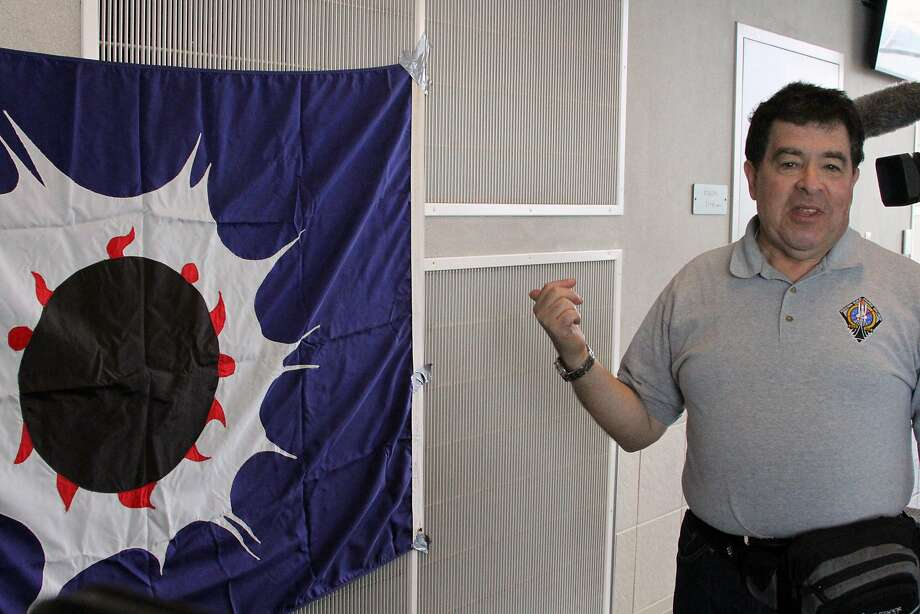 Craig Small, a semi-retired astronomer at the American Museum of Natural History's Hayden Planetarium in New York City,stands next to an eclipse flag in 1972 he hung at the Ted Stevens Anchorage International Airport  in Anchorage, Alaska, on Tuesday, March 8, 2016. He and other so-called eclipse chasers boarded a special flight from Anchorage to Honolulu to view the eclipse on Tuesday from the air. The eclipse will only be visible in parts of southeast Asia and the North Pacific Ocean, including the flight path of the Alaska Airlines flight. (AP Photo/Mark Thiessen) Photo: Mark Thiessen, AP