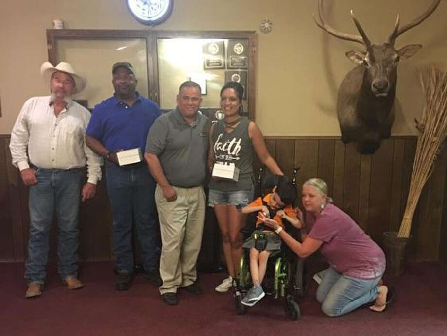 Izzy Ortiz, a special needs student at La Mesa Elementary, and his mother, Laurie Cruz, are shown with Plainview Elks members Greg Noel (left), Scott McKelvy, Paul Herrera and Mary O'Neil (knelling right). The men, along with David Gandy (not shown) provided funds needed to purchase three stabilizing handheld spoons which will allow Izzy, who suffers from cerebral palsy, to be able to feed himself.