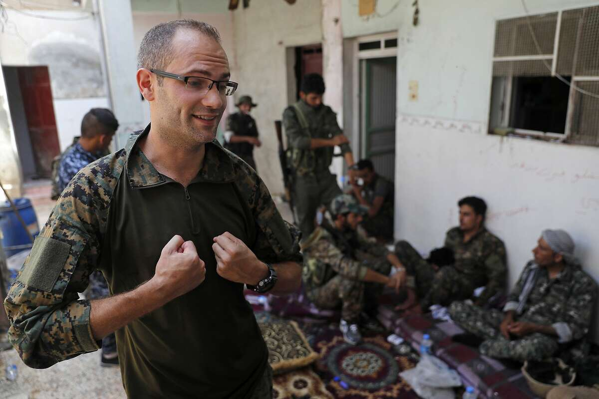 In this Monday, July 17, 2017 photo, Macer Gifford, a 30-year former City broker in London, who fights with an Assyrian militia, that is part of the U.S-backed forces battling Islamic State group militants, gives an interview to The Associated Press, on the western side of Raqqa, northeast Syria. Several U.S. and British volunteer fighters are on the front lines in the decisive battle against IS for the Syrian city of Raqqa. They joined the U.S.-allied militias in Syria for different reasons, some motivated by testimonies of survivors of the unimaginable brutality that IS flaunted in establishing its self-proclaimed caliphate. (AP Photo/Hussein Malla)