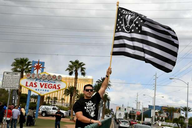 Oakland Raiders fan Matt Gutierrez of Nevada waves a Raiders flag in front of the Welcome to Fabulous Las Vegas sign after National Football League owners voted 31-1 to approve the team's application to relocate to Las Vegas during their annual meeting on March 27, 2017 in Las Vegas, Nevada. The Raiders are expected to begin play no later than 2020 in a planned 65,000-seat domed stadium to be built in Las Vegas at a cost of about USD 1.9 billion. (Photo by Ethan Miller/Getty Images)