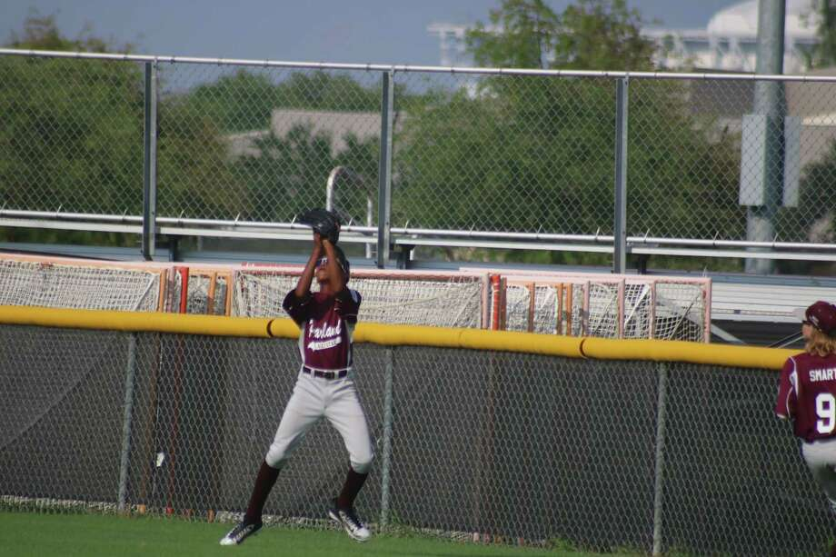Pearland East 11s outfielder Isaiah Castaneda hauls in a fly ball just inches from the outfield fence during the team's Sunday night win. It would prove to be the team's last win of the 2017 Little League season. Photo: Robert Avery