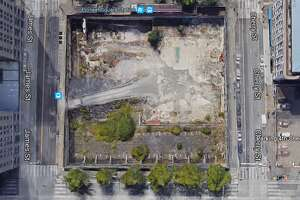 This image, from Google Earth, shows the hole in the ground across the street from City Hall that is, under a new deal sent to City Council Tuesday, set to finally be developed starting in 2019.