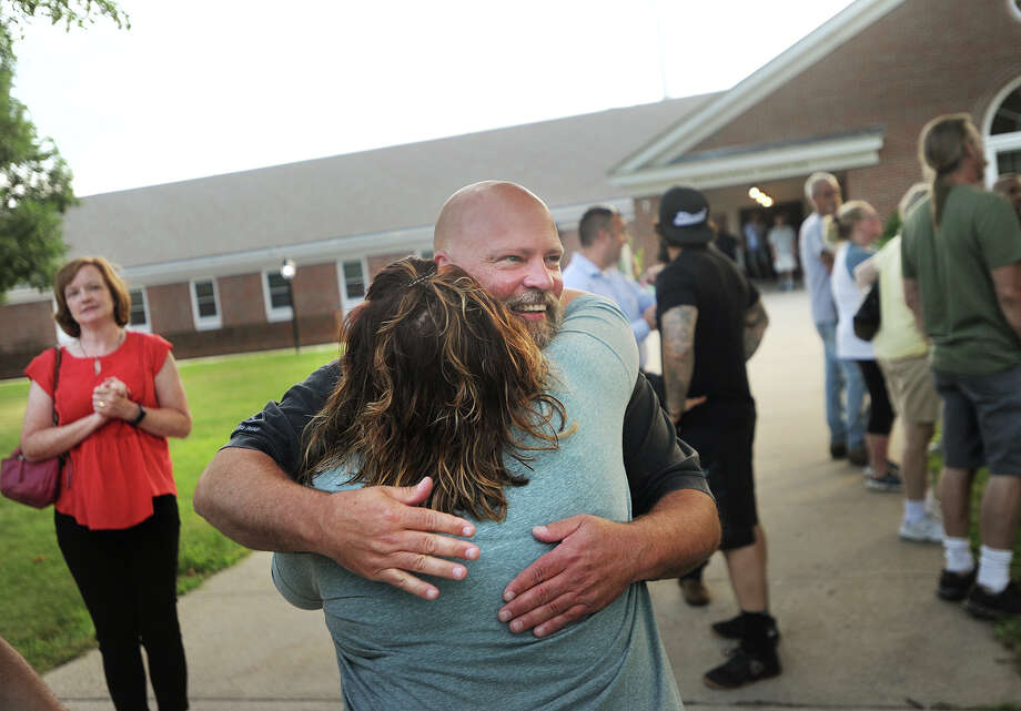 Monroe Police Officer Andrew Wall gets a hug from supporter Teresa Guerra, of Monroe, before his pre-termination hearing at Town Hall in Monroe, Conn. on Monday, July 17, 2017. Dozens came out in support of Wall, who was diagnosed and treated for brain cancer beginning in 2015 but now wants to return to work. Photo: Brian A. Pounds, Hearst Connecticut Media / Connecticut Post