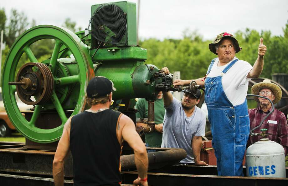 Rob Hall of Bay City, formerly an electrician with the Great Lakes Central Railroad, gives a thumbs up after successfully starting up an antique engine that was used in oil fields during the Midland Antique Engine Club's annual show on Friday in Merrill. Photo: (Katy Kildee/kkildee@mdn.net)