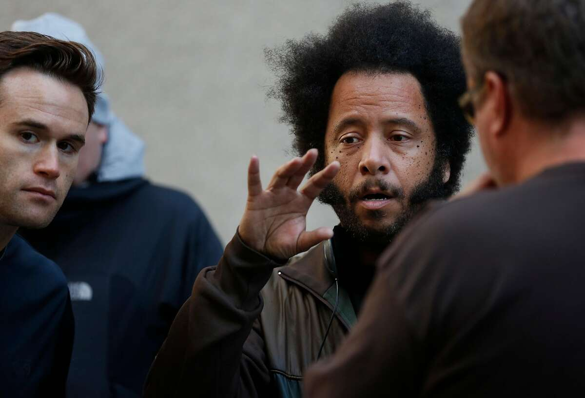 Director Boots Riley talks with his Director of Photography Doug Emmett, left, and Assistant Director Brian Benson, right, on the set of his film