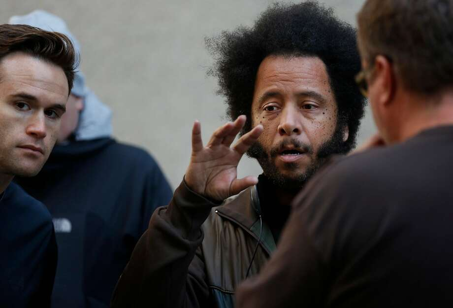 "Director Boots Riley talks with his Director of Photography Doug Emmett, left, and Assistant Director Brian Benson, right, on the set of his film  ""Sorry to Bother You"" between takes July 14, 2017 in downtown Oakland, Calif. Photo: Leah Millis, The Chronicle"