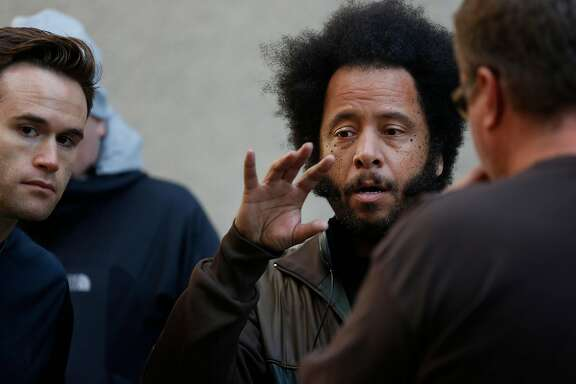 """Director Boots Riley talks with his Director of Photography Doug Emmett, left, and Assistant Director Brian Benson, right, on the set of his film  """"Sorry to Bother You"""" between takes July 14, 2017 in downtown Oakland, Calif."""