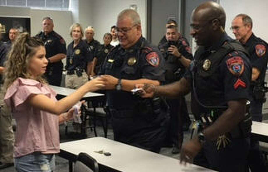 "Sam Houston State University student Liza Viera surprises Katy ISD police officers with Saint Michael's medallions, as part of her support campaign, ""Back the Blue – Liza's Mission."" Photo: Katy ISD"