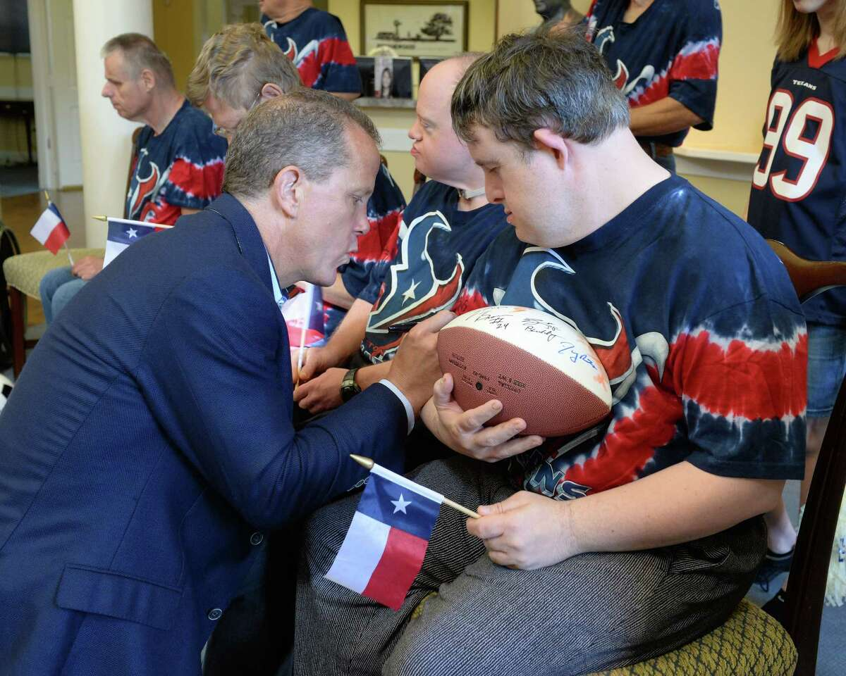 Houston Texans President Jamey Rootes signs an autograph for a resident of the Brookwood Community as Special Teams for Special Needs, a collaboration between the Houston Texans and Mustang Cat, present the Brookwood Community with a donation of $60,000 at the Brookwood Community in Brookshire, TX on July 11, 2017.