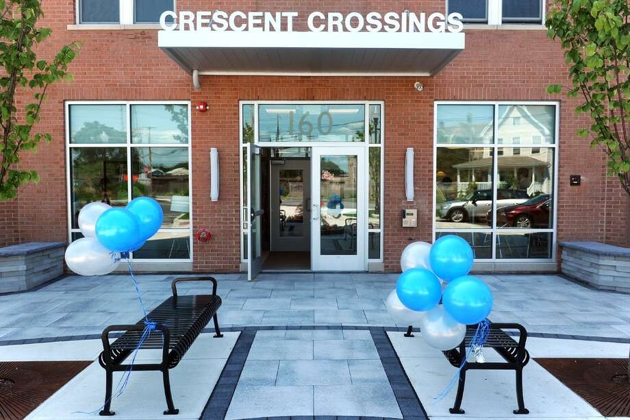 Balloons adorn the front of Crescent Crossing, a new affordable housing development in Bridgeport. Photo: Ned Gerard / Hearst Connecticut Media / Connecticut Post