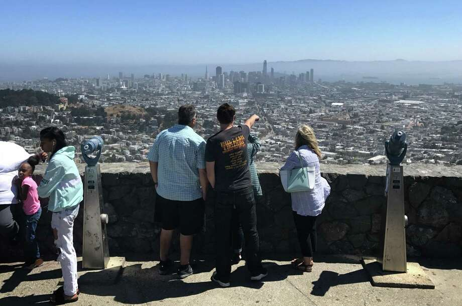 Visitors look out over San Francisco from Twin Peaks' Christmas Tree Point. Photo: Evan Sernoffsky / The Chronicle / Evan Sernoffsky/ The Chronicle