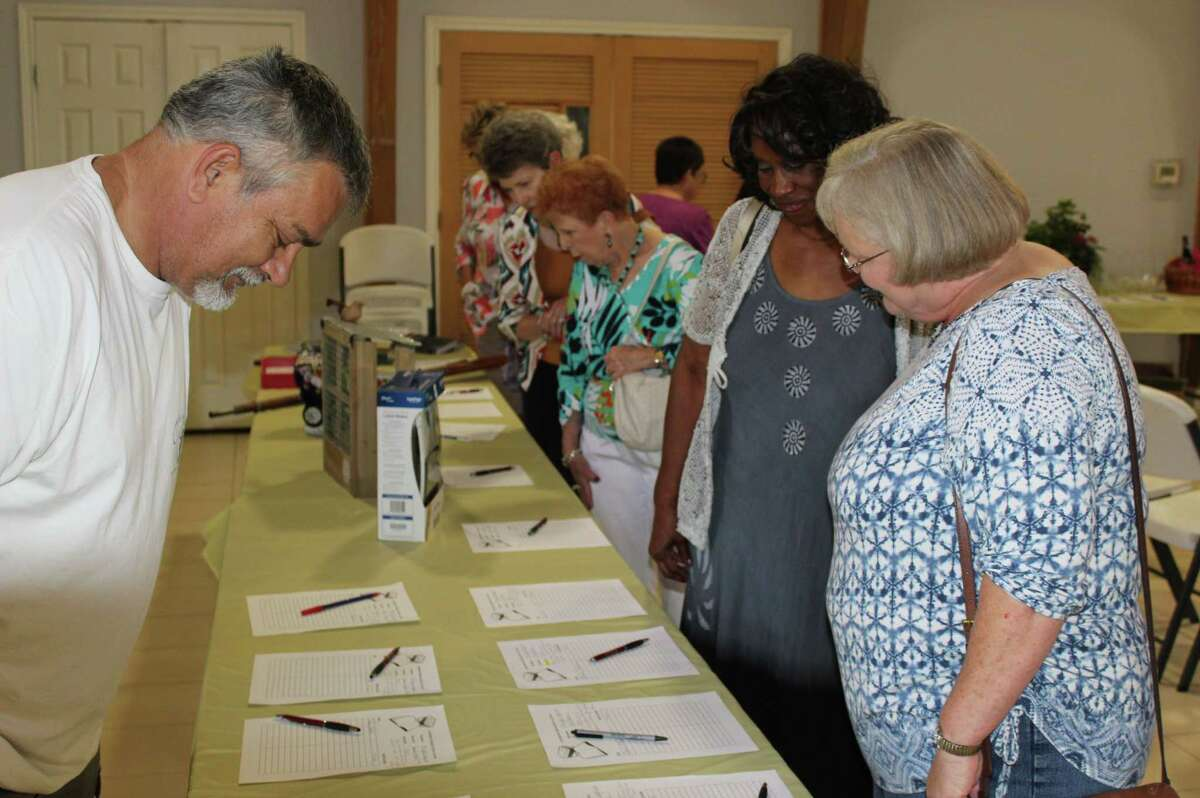 Visitors to the Annual Book Review look through the items up for silent auction.