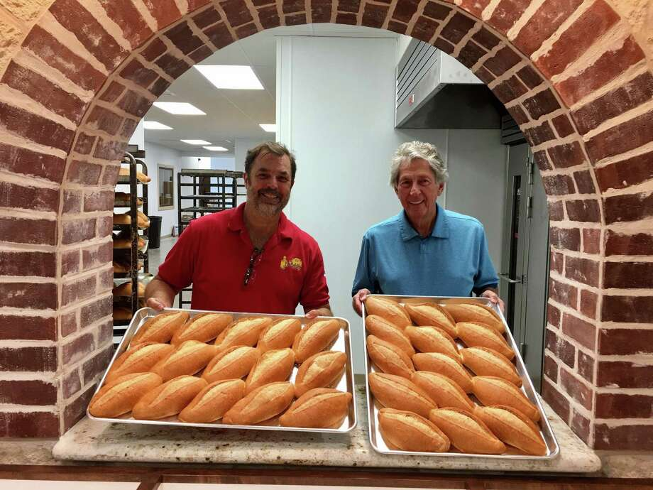 Kirk Michaelis and Bud Harmon hold the first batch of bolillos at the new El Bolillo Bakery on Southmore in Pasadena. Photo: Joey Guerra / Houston Chronicle