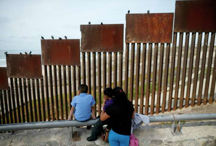 A family looks toward metal bars marking the U.S. border where it meets the Pacific Ocean in Tijuana, Mexico. (AP Photo file)