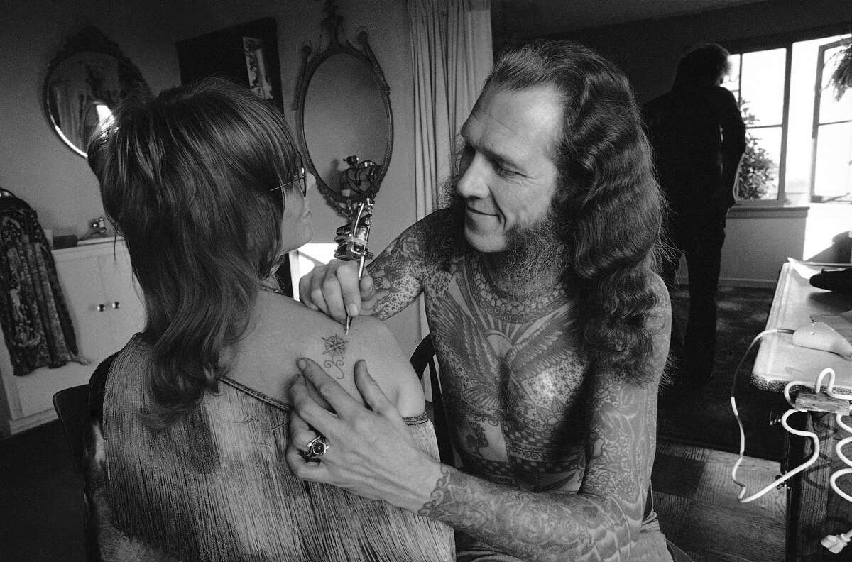 Tattoo artist Lyle Tuttle delicately embroiders Jutta Kay's shoulder with a cosmic flower tattoo in his Los Angeles office, Feb. 14, 1973.
