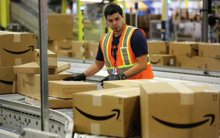 A worker at the Amazon Fulfillment Center in Schertz inspects packaging on a conveyor belt. Amazon pays the state sales tax only on direct sales but not from third-party sales that take place on its website.