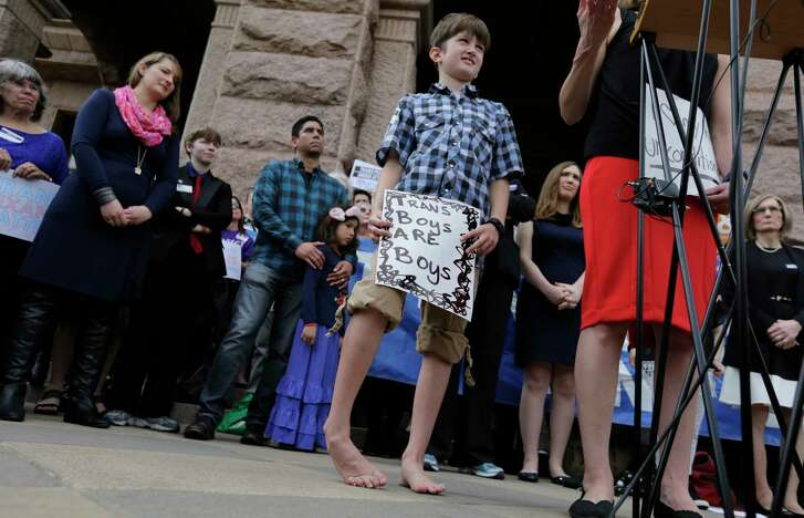"Max Briggle, right, holds a sign as he joins other members of the transgender community during a rally on the steps of the Texas Capitol, Monday, March 6, 2017, in Austin, Texas. The group is opposing a ""bathroom bill"" that would require people to use public bathrooms and restrooms that correspond with the sex on their birth certificate. (AP Photo/Eric Gay)"