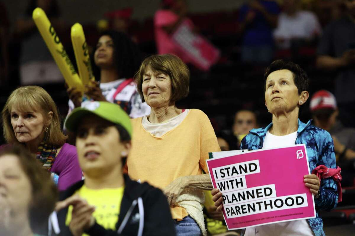 A woman holds a sign after a rally for Planned Parenthood held by the Seattle Storm before their game against the Chicago Sky, Tuesday, July 18, 2017 at KeyArena.