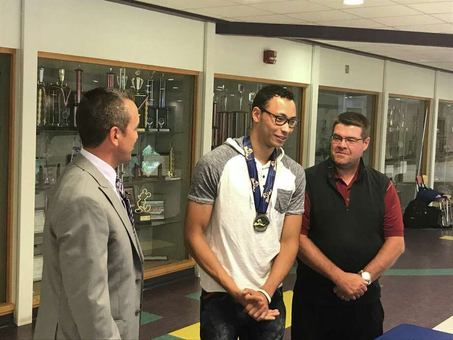 Former Amsterdam High track star Izaiah Brown, center, receives new medals from the New York State Public High School Athletic Association on Thursday, July 18, in Amsterdam. (Jason Franchuk / Times Union)