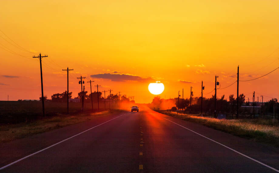 Pickup truck heading home at sunset on West Texas country road. Photo: Dszc/Getty Images