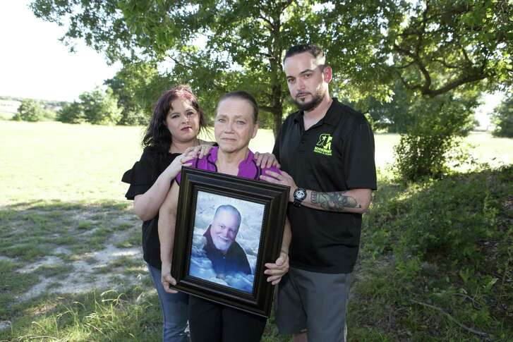 Shown are Stephanie Kingrey of West Texas (left), Sandra McCollum of Bellmead and Steve McCollum of Waco. Sandra McCollum is holding a portrait of her late husband, Larry McCollum, during a family reunion in June. Larry McCollum is among 22 people who have died as a result of indoor weather conditions at 15 state prisons since 1998, according to the Texas Department of Criminal Justice.