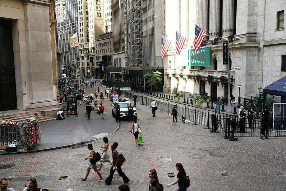 People walk past the New York Stock Exchange last month. San Antonio-based Harte Hanks Inc. previously has disclosed it could be subject to delisting from the NYSE because the company has been late in filing financial reports with the Securities and Exchange Commission. Photo: Spencer Platt /Getty Images / 2017 Getty Images