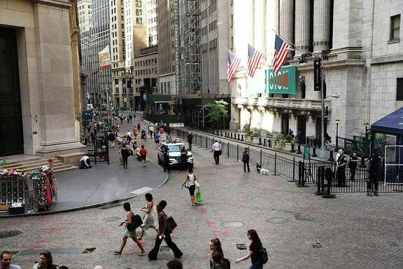 People walk past the New York Stock Exchange last month. San Antonio-based Harte Hanks Inc. previously has disclosed it could be subject to delisting from the NYSE because the company has been late in filing financial reports with the Securities and Exchange Commission.