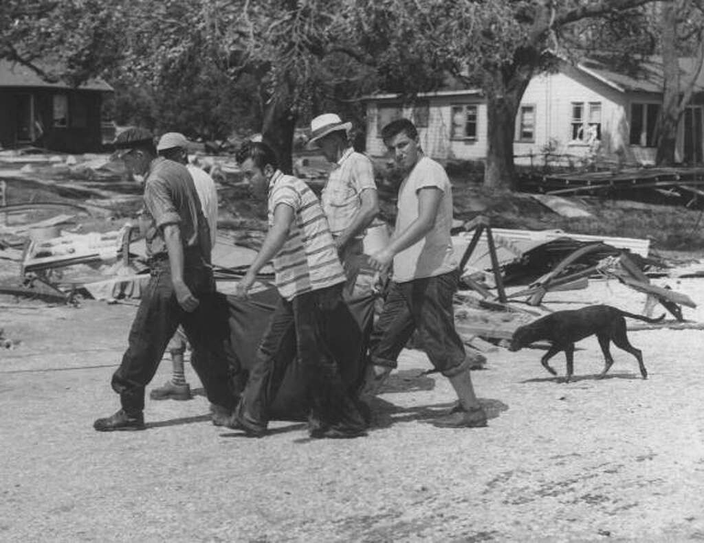 Carrying victim in bag to morgue from Hurricane Audrey's storm damage. Photo: Shel Hershorn