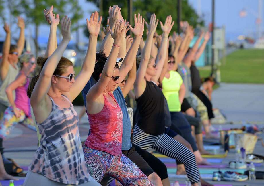 In this file photo, yoga enthusiasts participate in a class during the 4th annual Yoga Jam on the boardwalk at Harbor Point. Stamford Yoga Center will hold a class Saturday at its Spring Street studio to benefit survivors of violence. Photo: Matthew Brown / Hearst Connecticut Media / Stamford Advocate