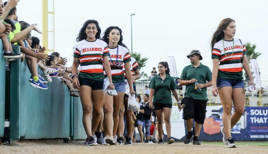 Softball players from across South Texas wave and toss out beads as they take a lap around Uni-Trade Stadium on Tuesday, July 18, 2017 during the opening ceremony of the PONY League Softball World Series. Photo: Danny Zaragoza