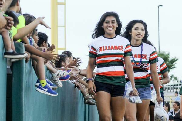 Softball players from across South Texas wave and toss out beads as they take a lap around Uni-Trade Stadium on Tuesday, July 18, 2017 during the opening ceremony of the PONY League Softball World Series.