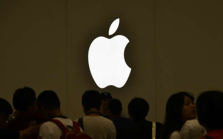Local residents line up under a Apple logo at the Taipei 101 building on July 1, 2017.  Apple opened its first store in Taiwan, drawing hundreds of excited fans to the shop located in the landmark skyscraper Taipei 101. / AFP PHOTO / SAM YEH        (Photo credit should read SAM YEH/AFP/Getty Images)