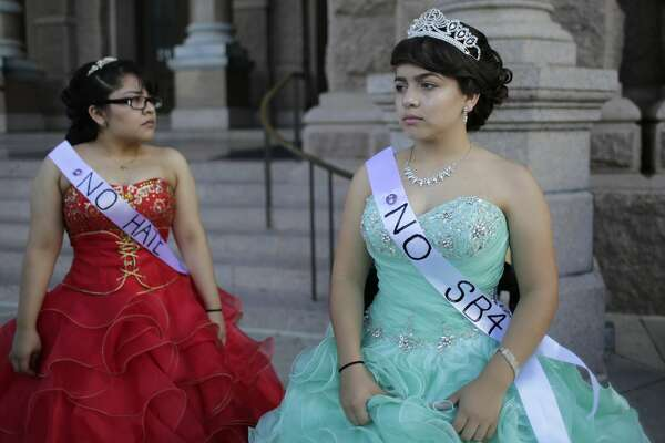 """Jennifer Ramirez, right, and Annie Ramirez, left, dress as Quinceaneras as they and others prepare to perform and protest SB4, an anti-""""sanctuary cities"""" bill, at the Texas Capitol in Austin, Texas, Wednesday, July 19, 2017. The """"sanctuary cities"""" ban, signed in May, lets police ask people during routine stops whether they're in the U.S. legally. (AP Photo/Eric Gay)"""