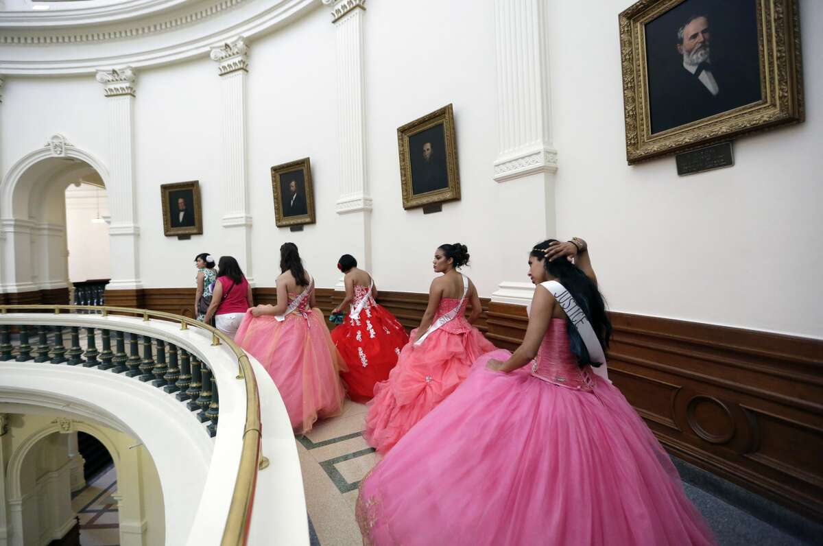 """Young women dressed as Quinceaneras walk through the Texas Capitol to visit lawmakers as they protest SB4, an anti-""""sanctuary cities"""" bill, in Austin, Texas, Wednesday, July 19, 2017. The """"sanctuary cities"""" ban, signed in May, lets police ask people during routine stops whether they're in the U.S. legally. (AP Photo/Eric Gay)"""