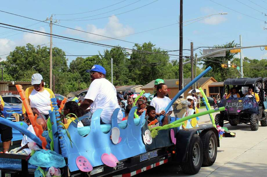 Parade participants smile and show their spirit from decorated parade floats as they pass by spectators during the annual Barrett Station Homecoming Parade on Saturday, July 15. Photo: Melanie Feuk