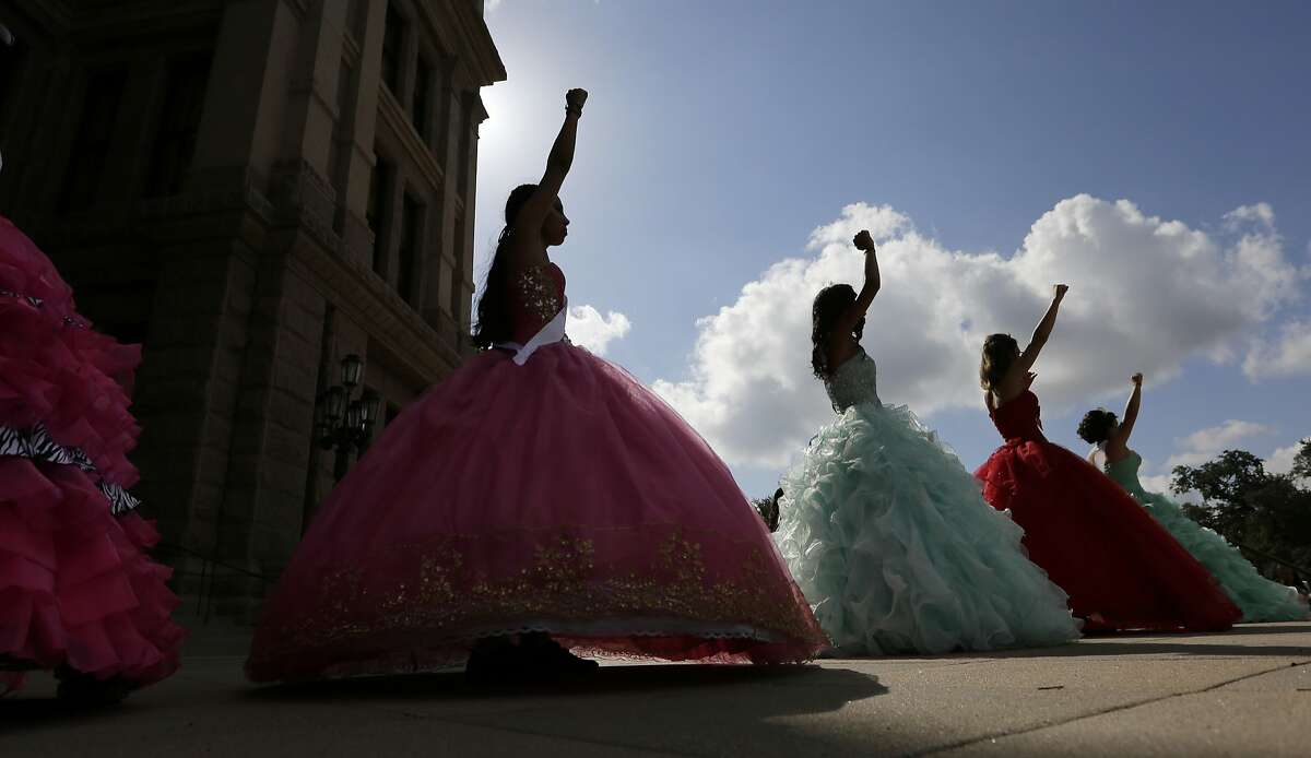 Young women dressed as Quinceaneras perform and protest SB4, an anti-