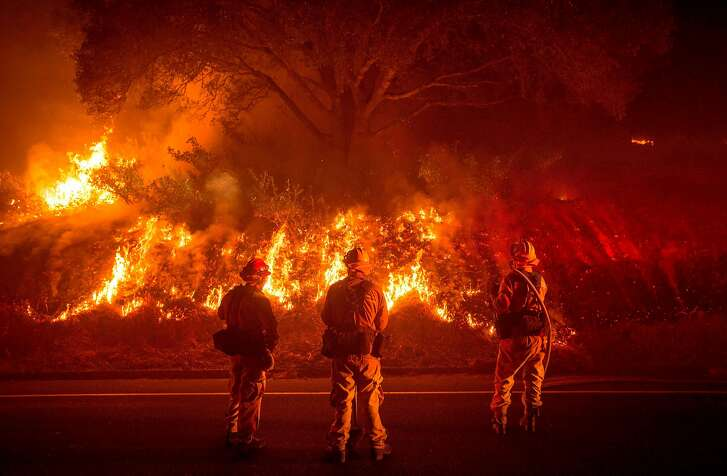 Firefighters monitor flames on the side of a road as the Detwiler fire rages on near the town of Mariposa, California on July 18, 2017. California has suffered widespread fires in recent days, with a lighting strike near Yosemite National Park sparking a blaze that destroyed more than 26 square kilometers (10 square miles) of forest. / AFP PHOTO / JOSH EDELSONJOSH EDELSON/AFP/Getty Images