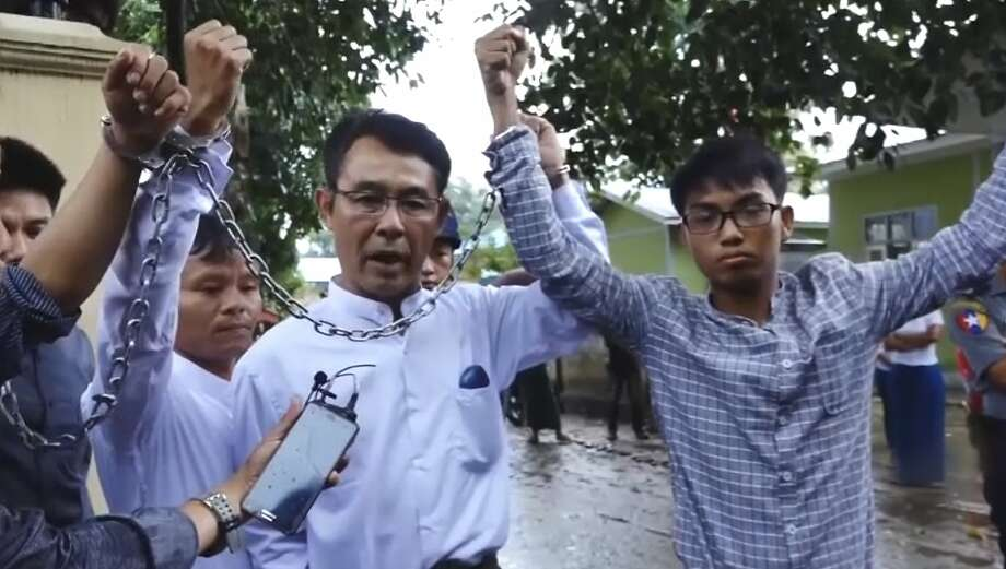 Journalists show their shackles after being arrested under Myanmar's Unlawful Associations Act. Photo: Associated Press