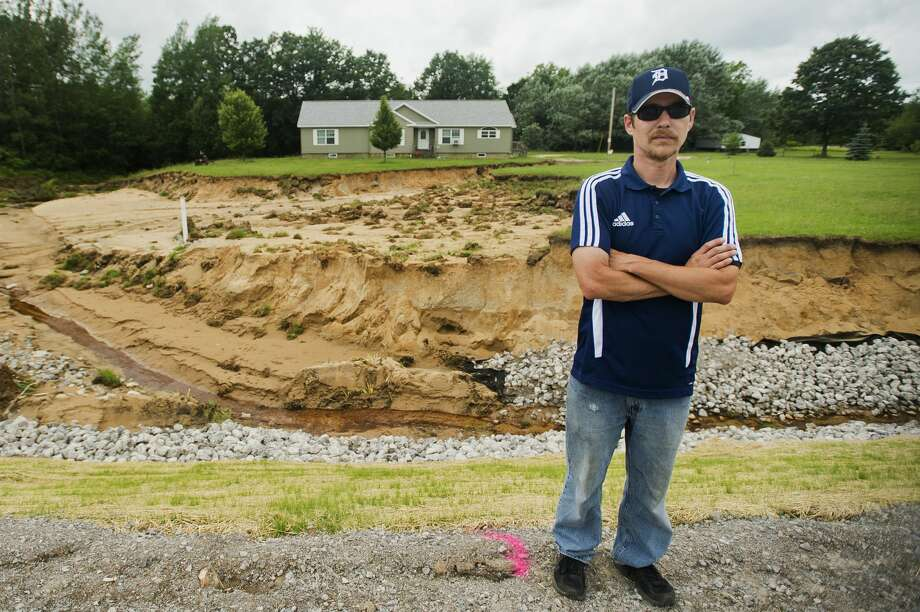 Billy Bryant poses for a portrait in front of the home he shared with his wife Kelly and son Gabriel, 11, before recent flooding washed away the majority of the front yard, as well as a basement wall and back porch, on Thursday, July 13, 2017 on Coleman Road near M-20. Photo: (Katy Kildee/kkildee@mdn.net)