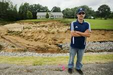 Billy Bryant poses for a portrait in front of the home he shared with his wife Kelly and son Gabriel, 11, before recent flooding washed away the majority of the front yard, as well as a basement wall and back porch, on Thursday, July 13, 2017 on Coleman Road near M-20.