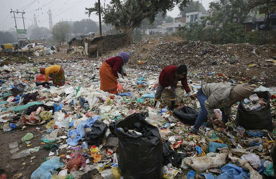 People wade through plastic and other refuse at a garbage dump in Lucknow, India, searching for reusable materials in 2016. Photo: Rajesh Kumar Singh, Associated Press