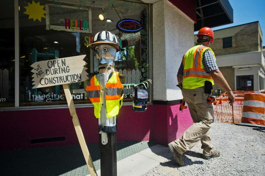 Project Manager Dennis Lauer walks past Imagine That! and a construction worker mannequin in front of the store as crews work on the Main Street streetscape project on Thursday. Businesses on Main Street will remain open as work is done to update sidewalks, street lighting, landscaping and irrigation. Photo: (Katy Kildee/kkildee@mdn.net)