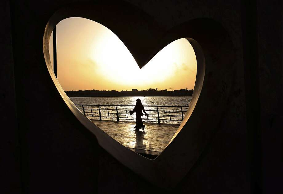 FILE -- In this May 11, 2014 file photo, a Saudi woman seen through a heart-shaped statue walks along an inlet of the Red Sea in Jiddah, Saudi Arabia. A young Saudi woman has sparked a sensation online by posting a video of herself in a miniskirt and crop top walking around in public, with some Saudis calling for her arrest and others rushing to her defense. The video, first shared on Snapchat, shows her walking around an empty historic fort in Ushaiager, a village north of the capital, Riyadh, in the desert region of Najd, where many of Saudi Arabia's most conservative tribes and families are from. (AP Photo/Hasan Jamali, File) Photo: Hasan Jamali, Associated Press