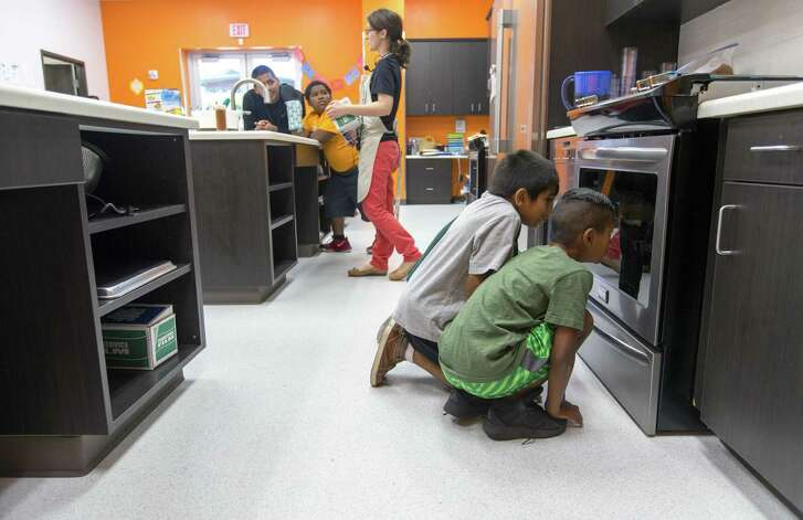A.J. Cantu, front, and Jayden Rodriguez watch as the crusted chicken strips they made bake in the kitchen of their Boys & Girls Clubs clubhouse.
