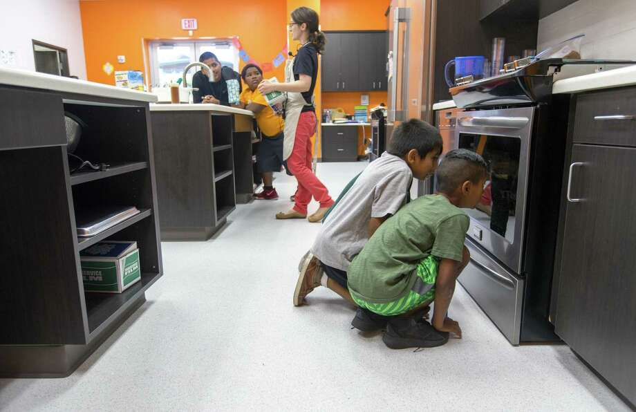 A.J. Cantu, front, and Jayden Rodriguez watch as the crusted chicken strips they made bake in the kitchen of their Boys & Girls Clubs clubhouse. Photo: William Luther /San Antonio Express-News / © 2017 San Antonio Express-News